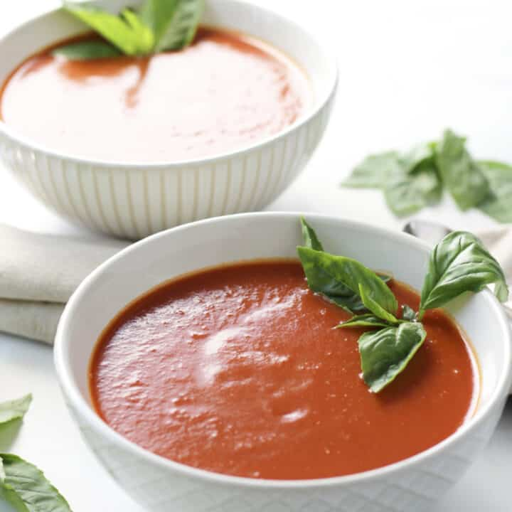 two white bowls of shimmering red soup, garnished with fresh basil