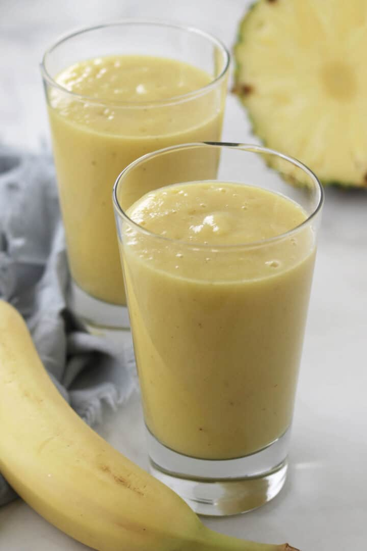 two glasses of creamy yellow smoothie with part of a banana and a cut pineapple around them